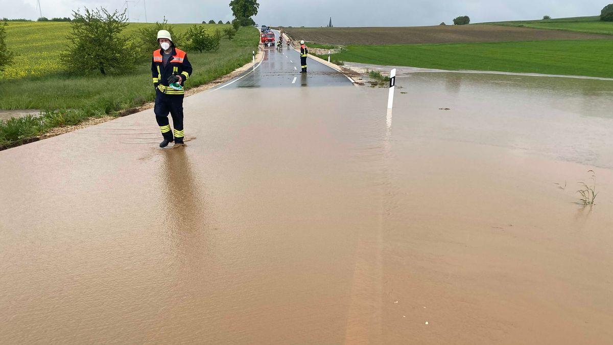 Ein Feuerwehrmann läuft an einer komplett überfluteten Straße entlang.