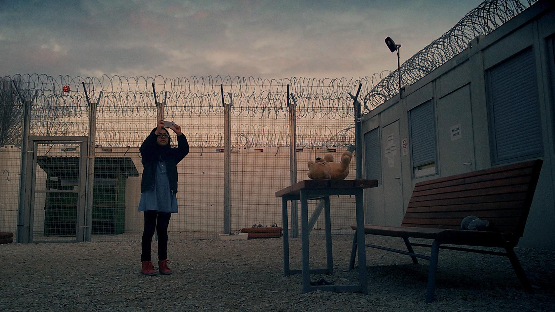 """Filmstill aus """"Midnight Traveler"""": Mädchen steht mit einem Handy auf dem Hof einer Flüchtlingsunterkunft und fotografiert"""