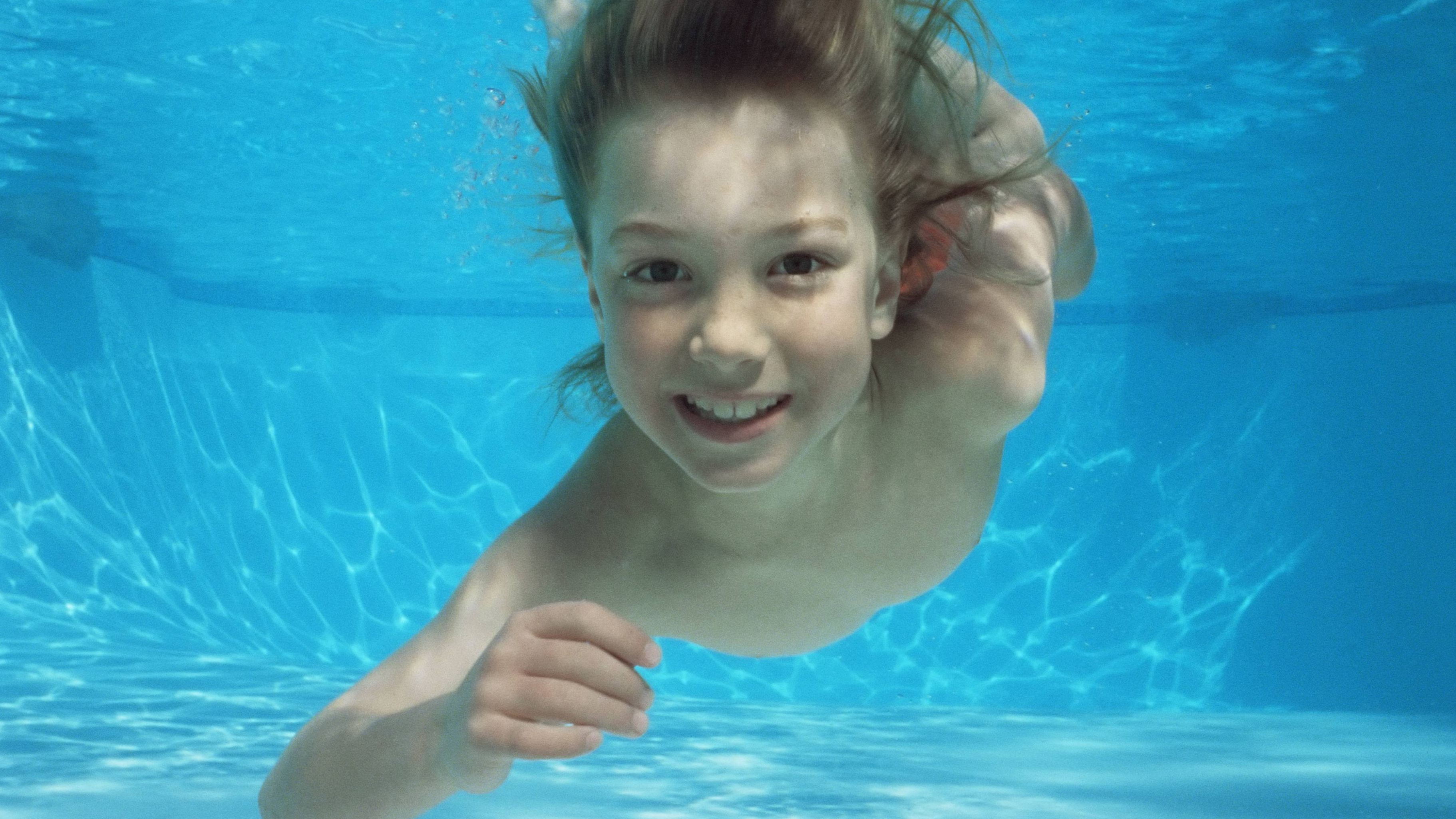 Ein Kind taucht in einem Pool, es lächelt in die Kamera.