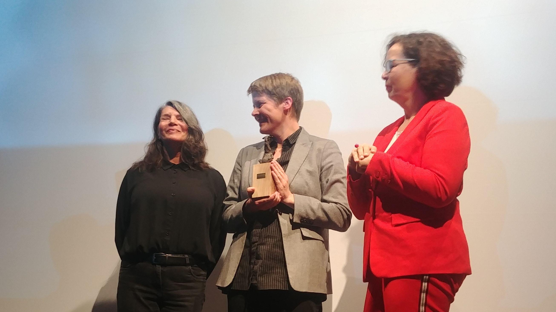 Verleihung des Nürnberger Menschenrechtsfilmpreises. Festivalleiterin andrea Kuhn mit dem Preis in der Mitte.