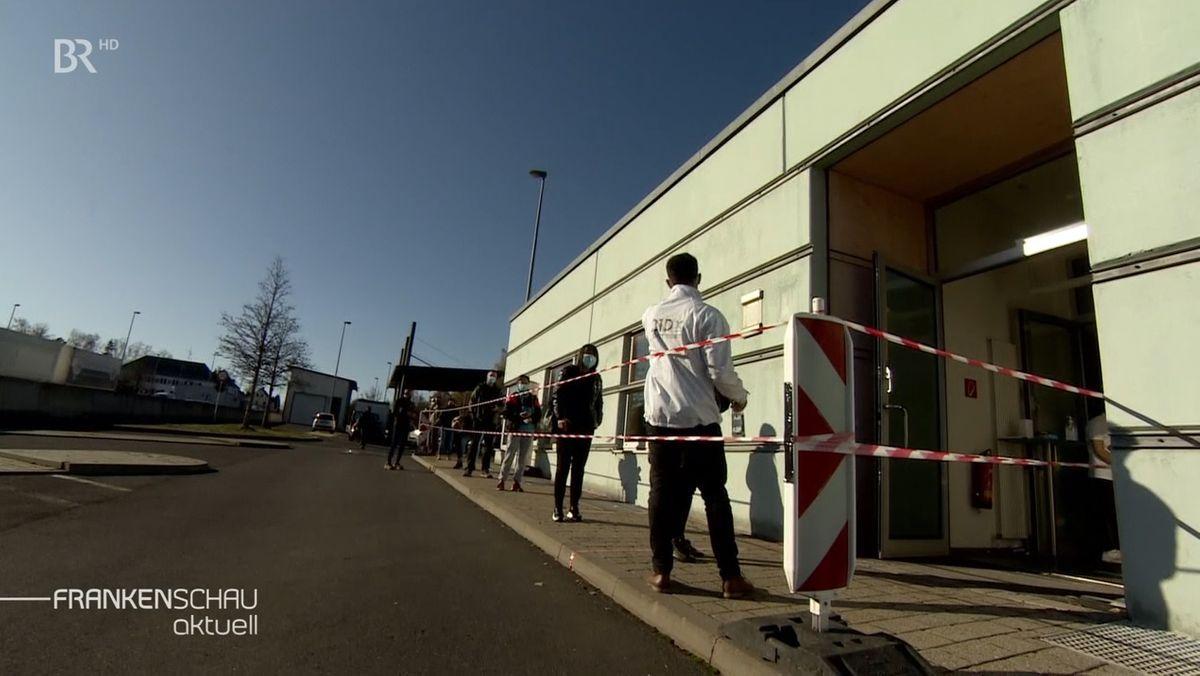 Personen mit Mud-Nasen-Schutz stehen hinter einem weiß-rotem Absperrband vor dem Eingang eines Gebäudes und warten.