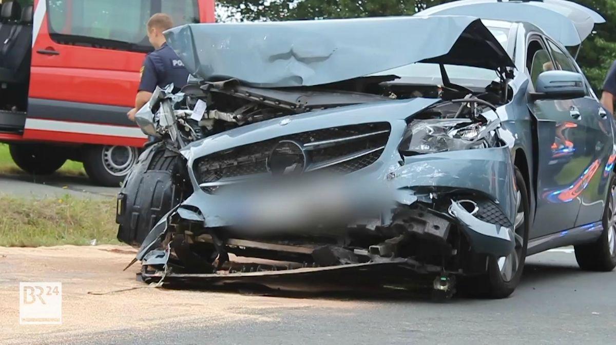 Ein auto steht schwer beschädigt auf der Universitätsstraße in Bayreuth.