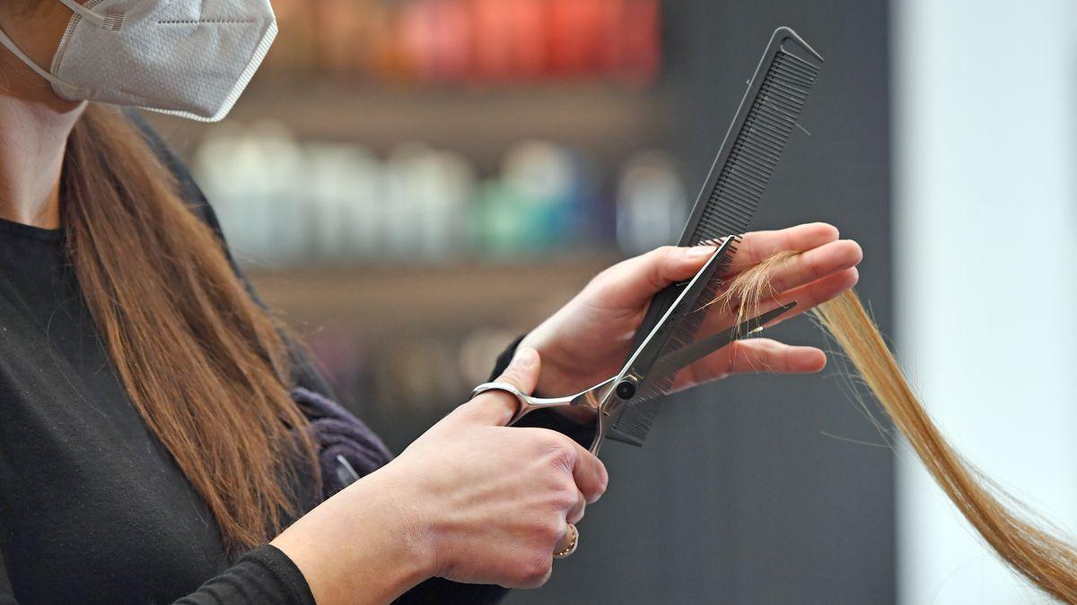 Ein Frau schneidet mit FFP2-Maske einem Kunden die Haare (Symbolbild)