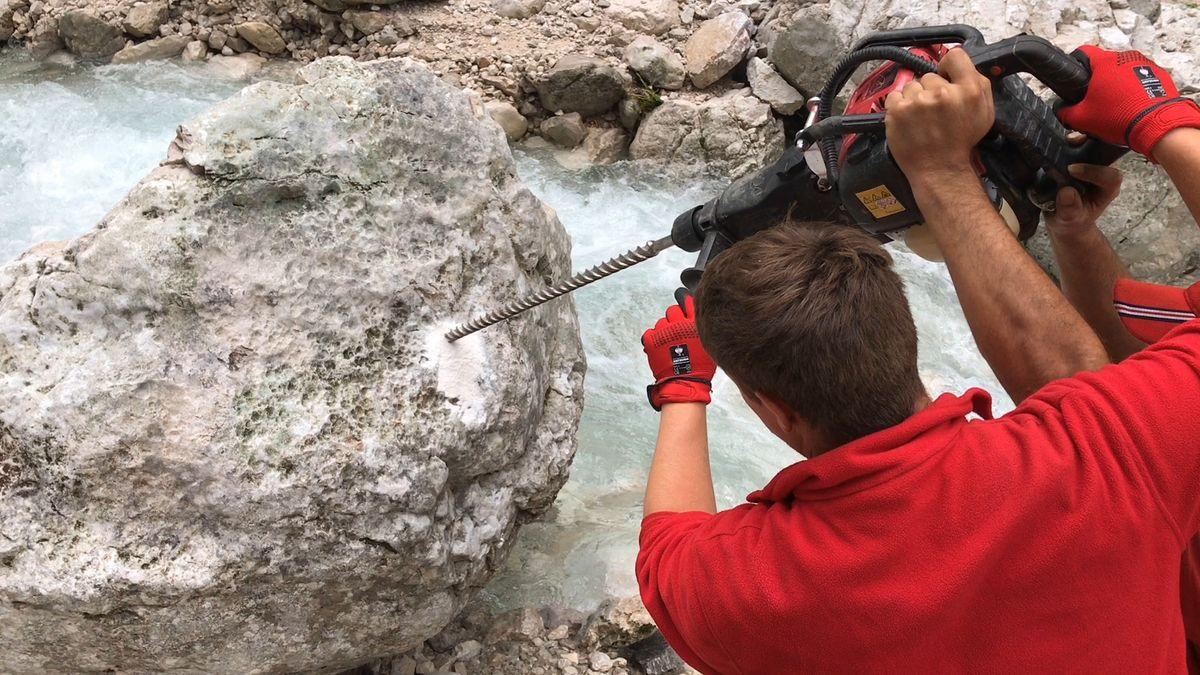 Mitglieder des Aufräumtrupps bohren ein Loch in einen Felsbrocken