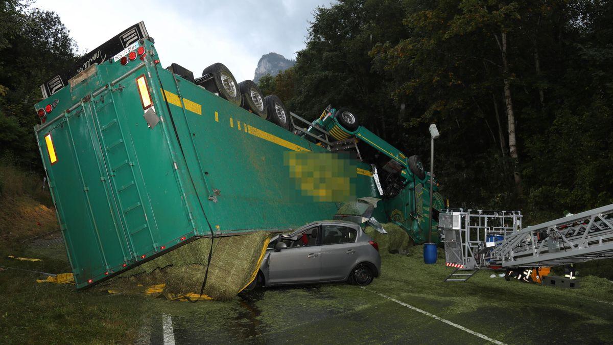 Auf der B 23 bei Oberammergau liegt ein türkisgrüner Lastwagen auf dem Dach quer über die Straße. Die Heuballen, die der Laster geladen hat, sind überall verteilt. Zur Hälfte unter dem Laster begraben ist ein kleines graues Auto.