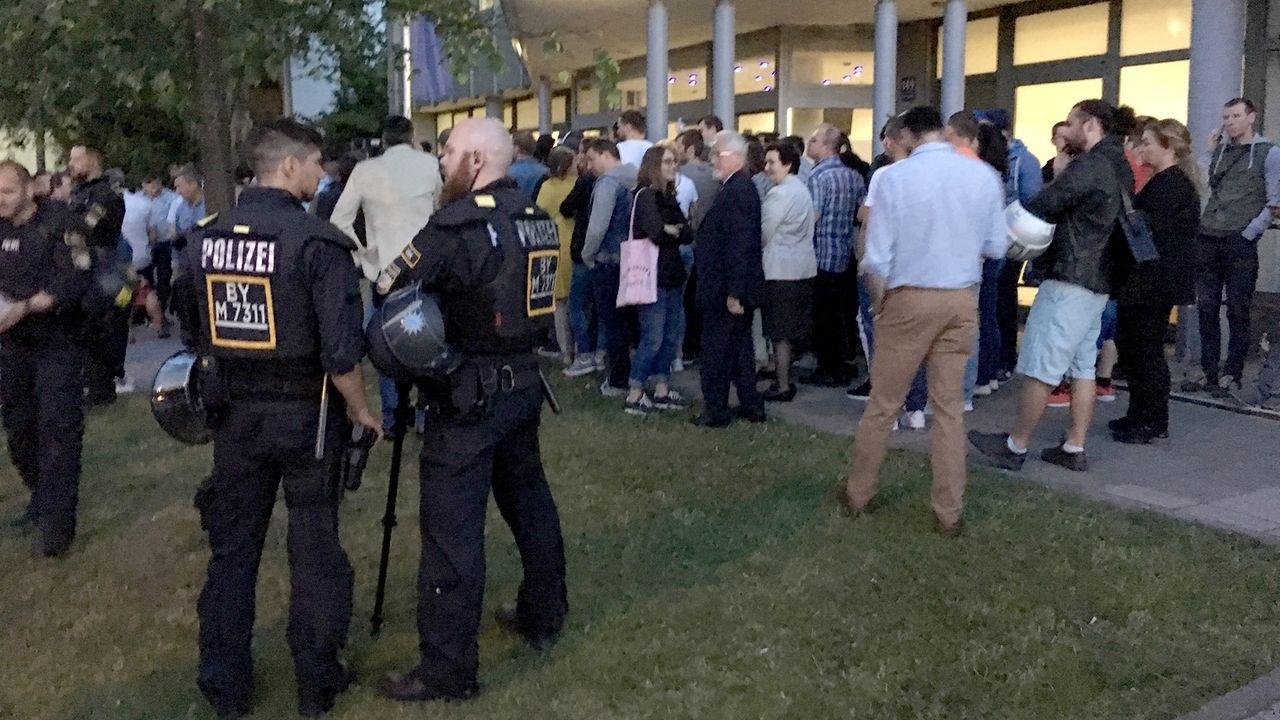Rumänen stehen vor dem rumänischen Konsulat in München, um ihre Stimme für die Europawahl abzugeben. Daneben stehen Polizisten.