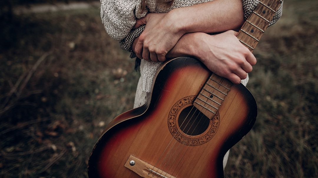 Ein Mann hält eine Gitarre.