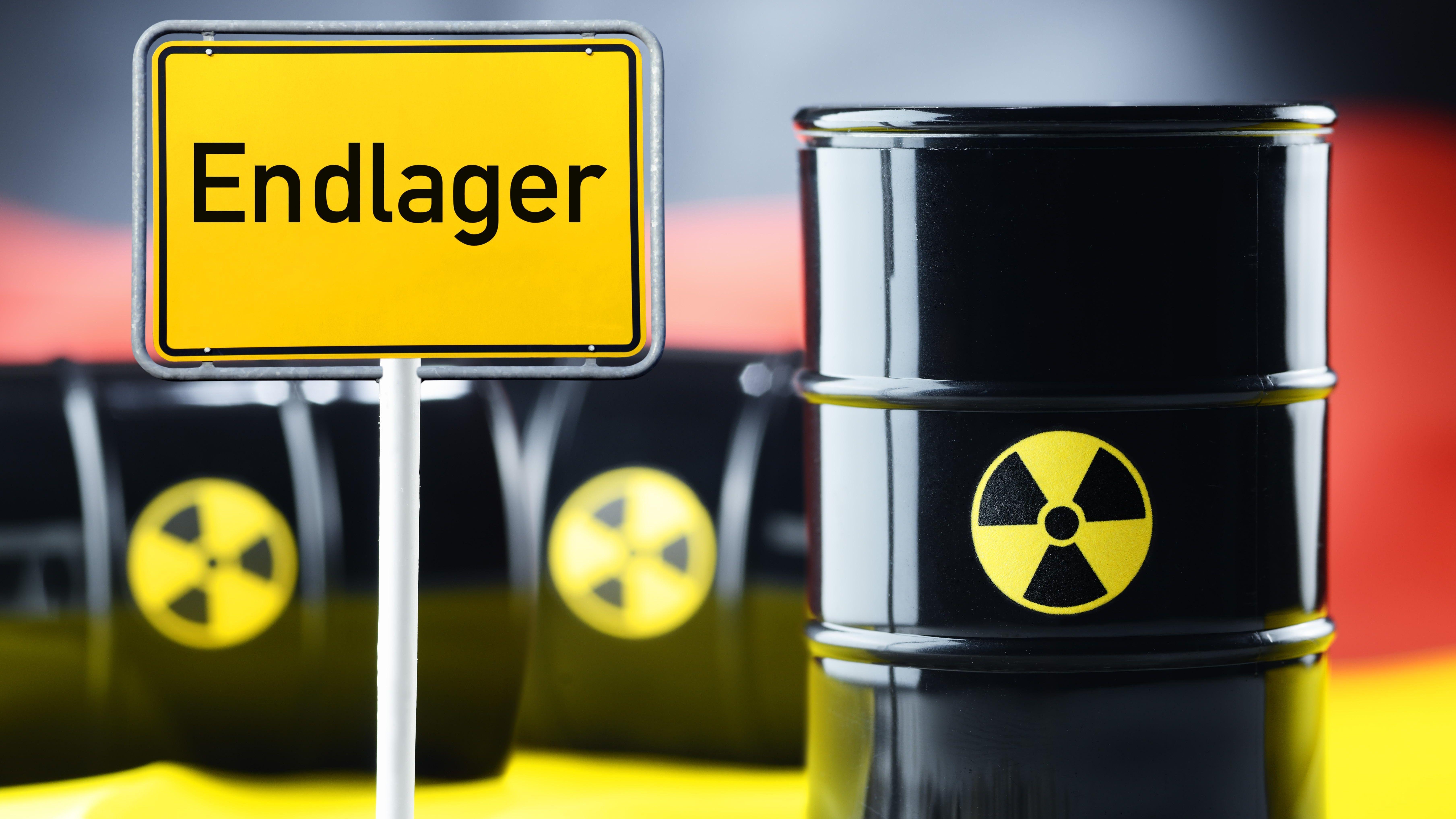 Drei Atommüll-Fässer vor einer Deutschlandfahne und Ortsschild mit Aufschrift Endlager