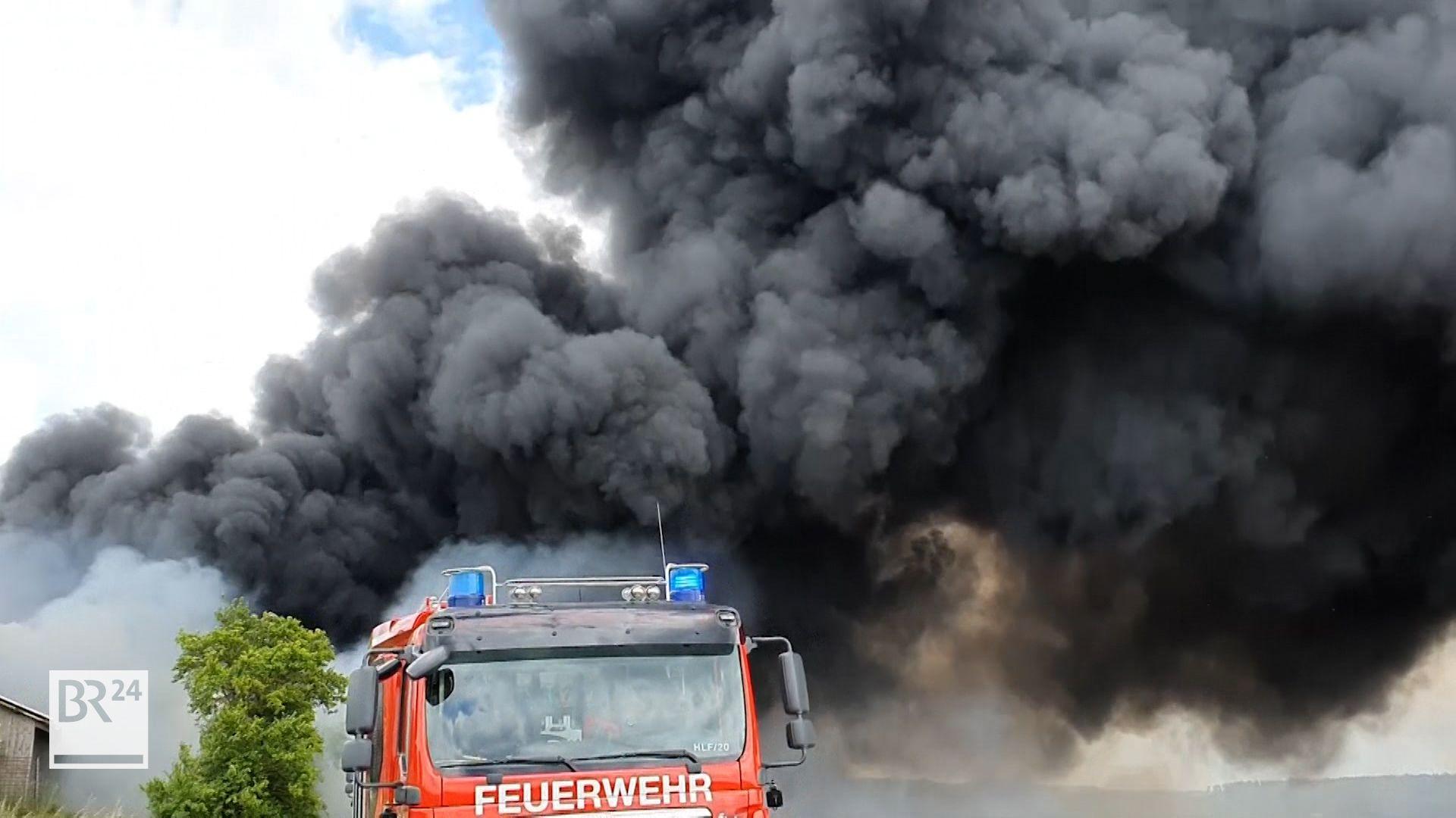 Große, schwarz-graue Rauchwolke steigt in den Himmel auf. Im Vordergrund sind  am unteren Bildrand ein Feuerwehreinsatzwagen und ein Baum jeweils zur Hälfte zu sehen.