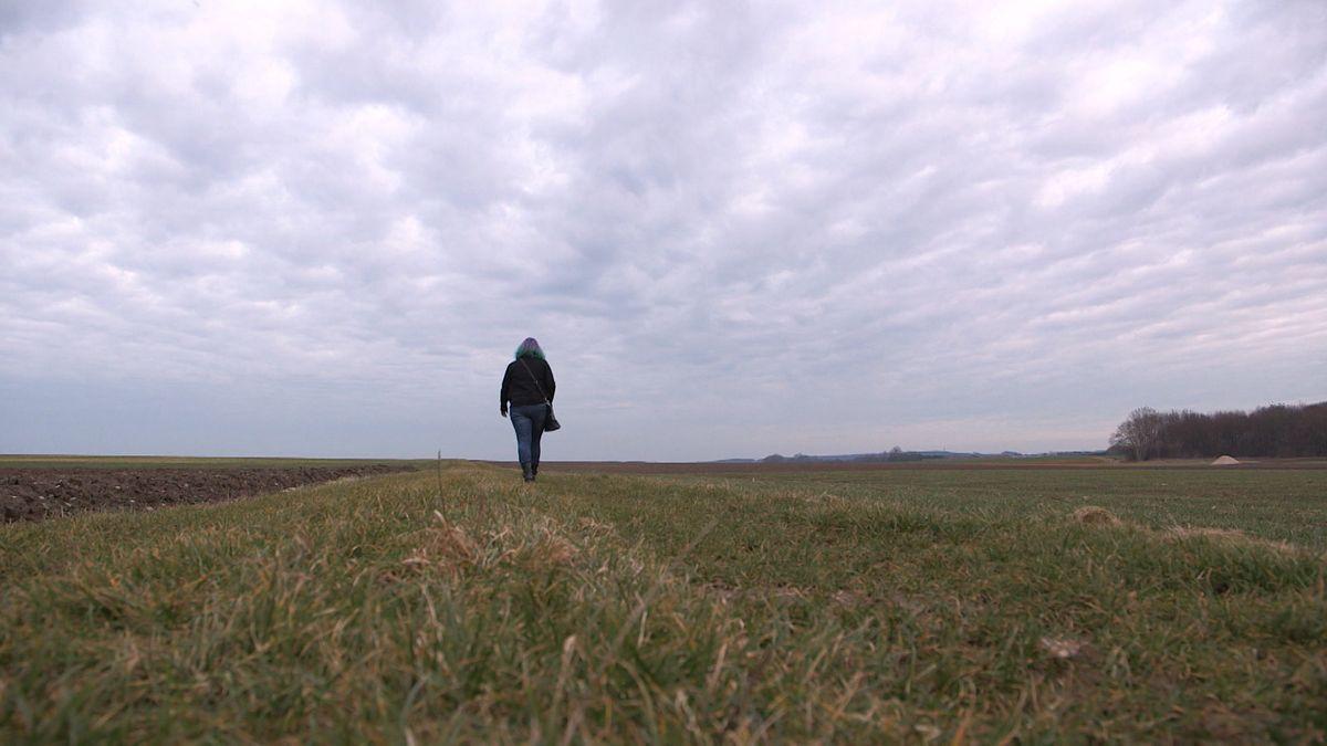 Eine Frau geht auf einer Wiese zwischen Feldern spazieren.
