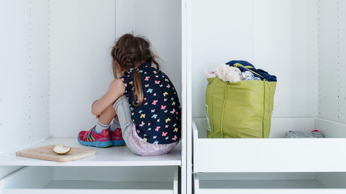 Ein Mädchen kauert in einer Schrankecke mit dem Rücken zum Betrachter.