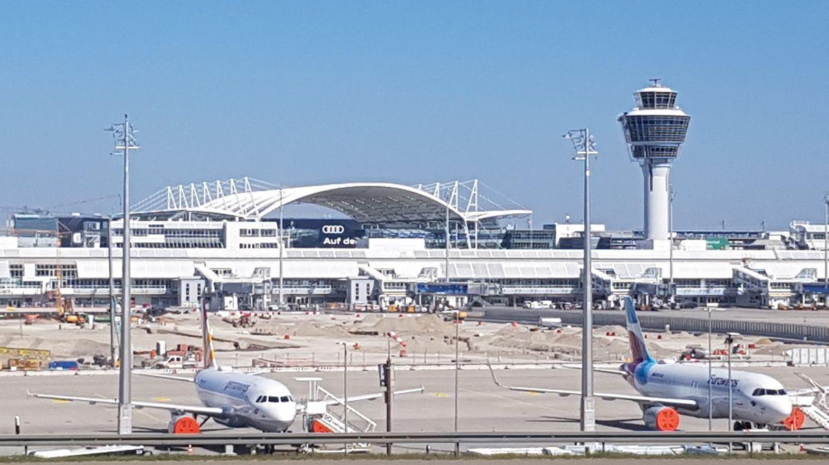 Flughafengebäude und Tower mit geparkten Flugzeugen