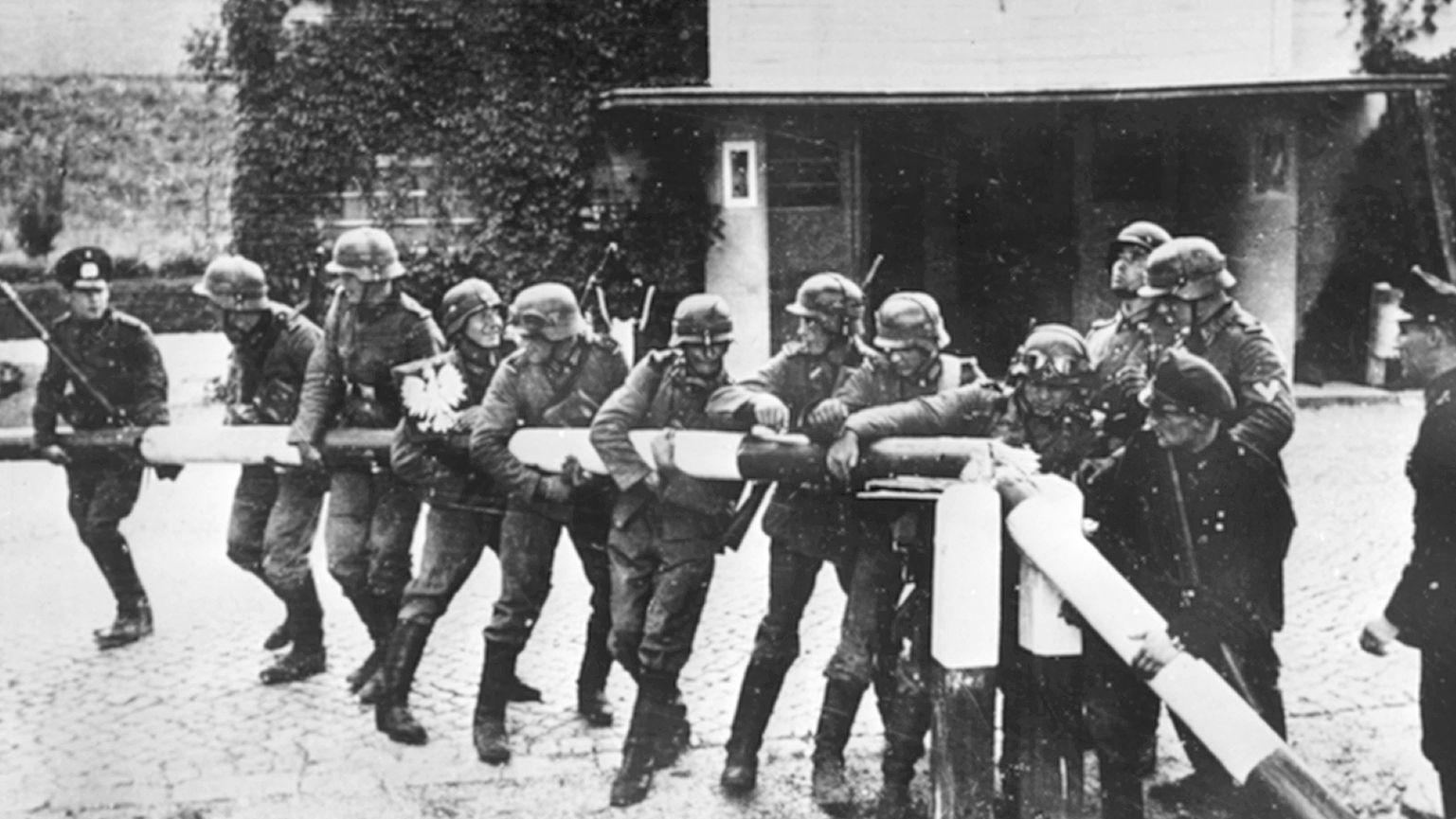 Einmarsch in Polen: Am 01.09.1939 reißen Soldaten der deutschen Wehrmacht einen rot-weißen Schlagbaum an der deutsch-polnischen Grenze nieder.