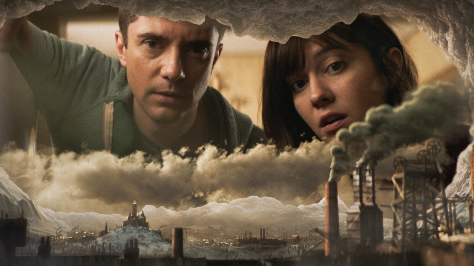 Ein Mann und eine Frau blicken auf eine Miniaturstadt