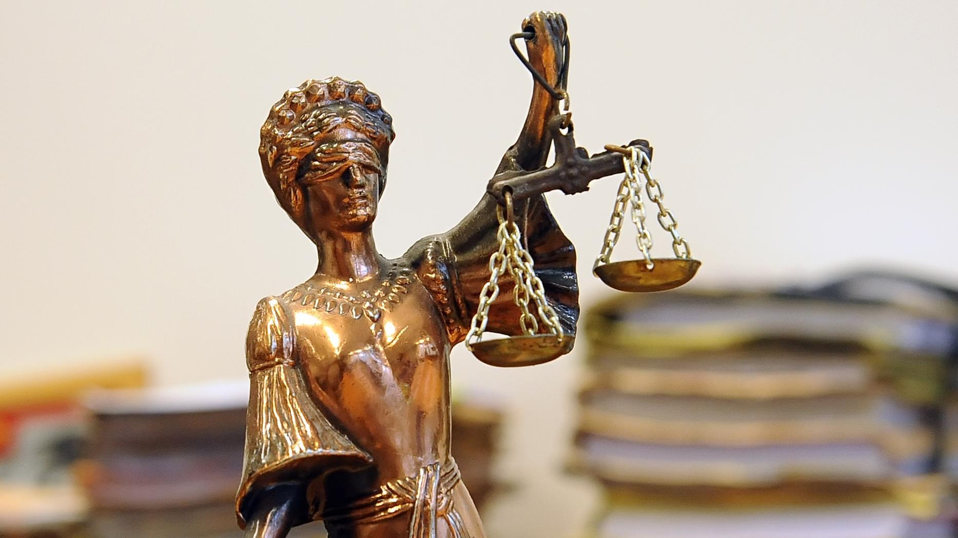 Eine goldfarbene Justitia-Figur vor Aktenbergen