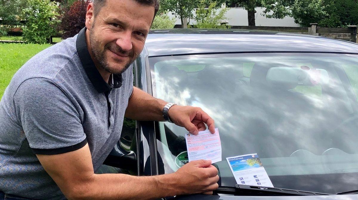 Ein Mann befestigt einen Zettel an der Windschutzscheibe eines Autos