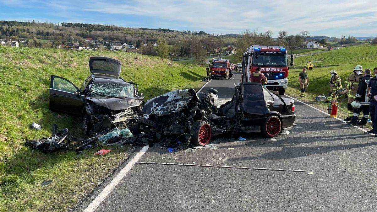 Schwerer Unfall: Zwei völlig zerstörte Autos stehen auf einer Straße und daneben.