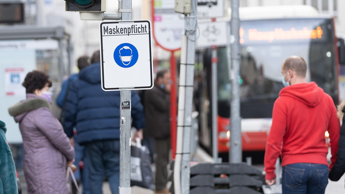 Ein Schild informiert über die Maskenpflicht in einer deutschen Innenstadt, zwei Passanten tragen Mund-Nasen-Schutz. Das Foto entstand am 23. Oktober 2020 in Osnabrück.