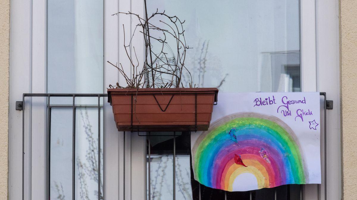 An einem Fenster hängt ein gemaltes Bild von einem Regenbogen.