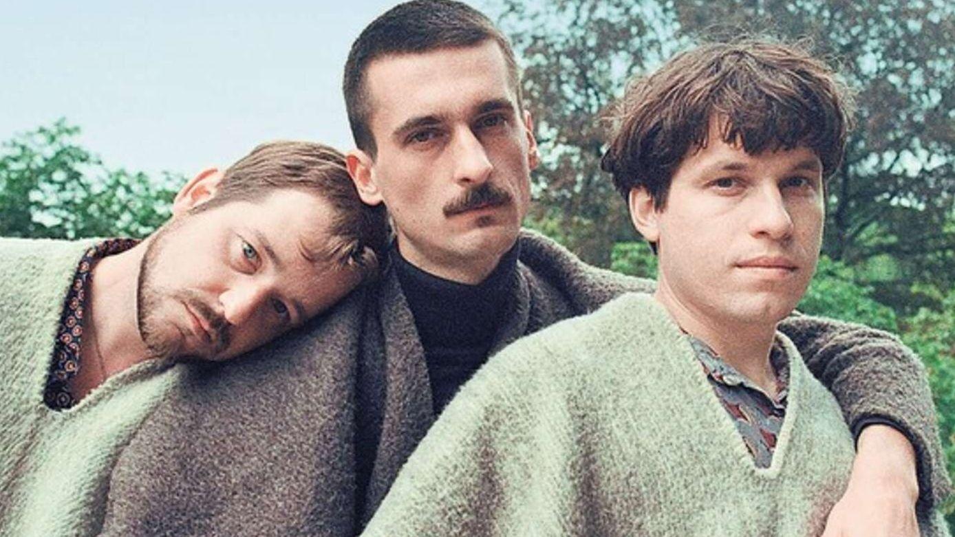 Drei junge Männer, in Ponchos gewandet, lehnen sich aneinander.