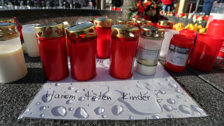 """""""Warum töten Kinder?"""" steht am Königsplatz auf einem Zettel zwischen Grablichtern an der Stelle, wo ein Feuerwehrmann bei einer Auseinandersetzung mit Jugendlichen tödlich verletzt worden war."""
