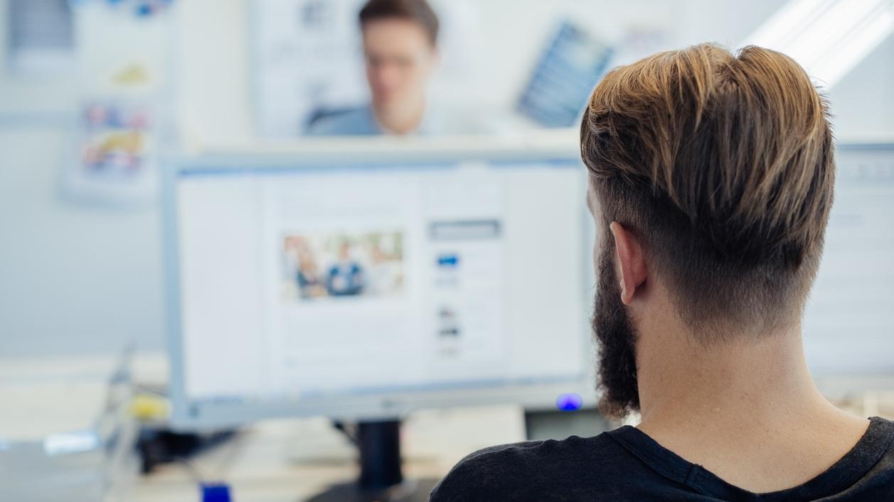 Büromitarbeiter von hinten am PC