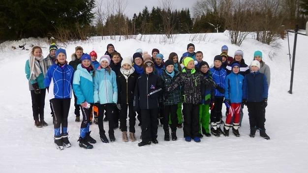 Schüler und Schülerinnen stehen in Ski-Klamotten im Schnee.