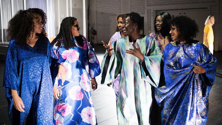 Eine Gruppe dunkelhäutiger Frauen in blauen Gewändern unterhält sich