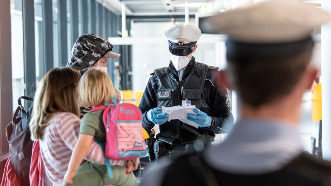 Polizisten kontrollieren eine Familie bei der Einreise nach Deutschland