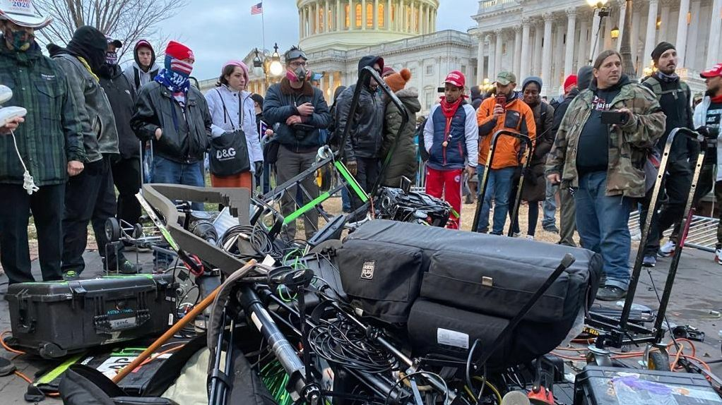 Eine Menschenmenge hat Kamera-Equipment von einigen Medien zerstört