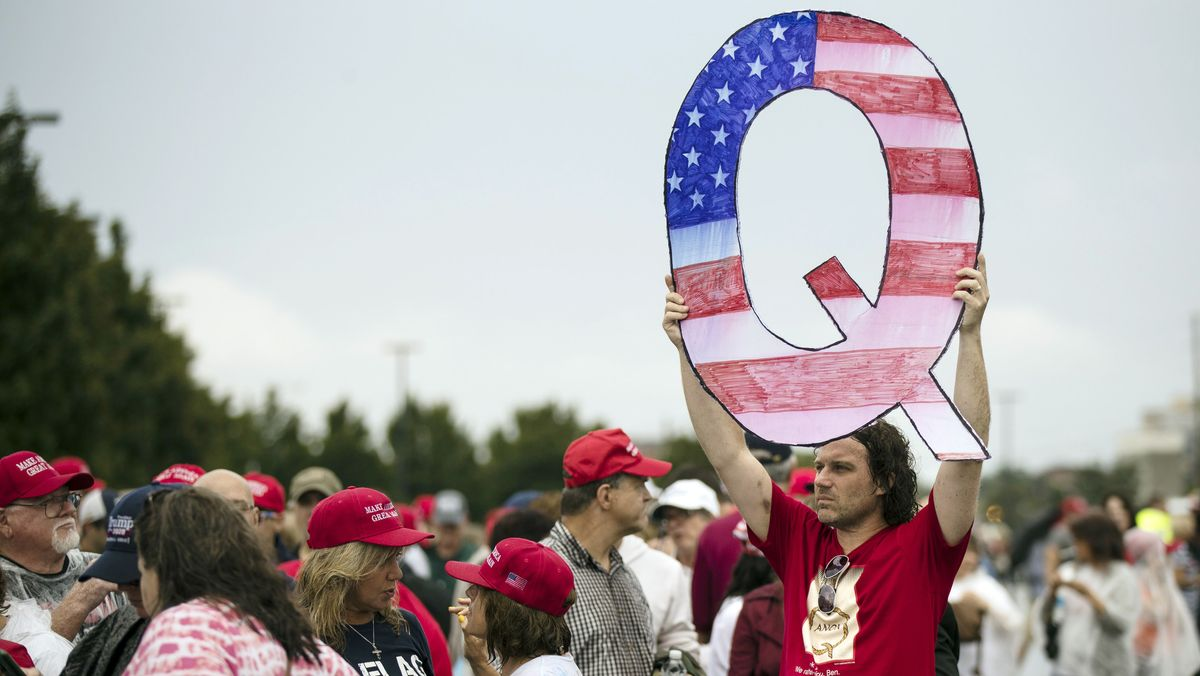 """Mann in Menschenmenge hält ein """"Q"""" in den Farben der US-Flagge hoch"""