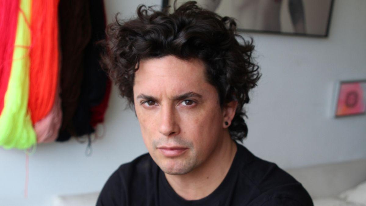 Der Schriftsteller Benjamin Labatut sitzt in einem Wohnzimmer und blickt kritisch in die Kamera