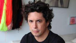 Der Schriftsteller Benjamin Labatut sitzt in einem Wohnzimmer und blickt kritisch in die Kamera | Bild:Juana Gomez