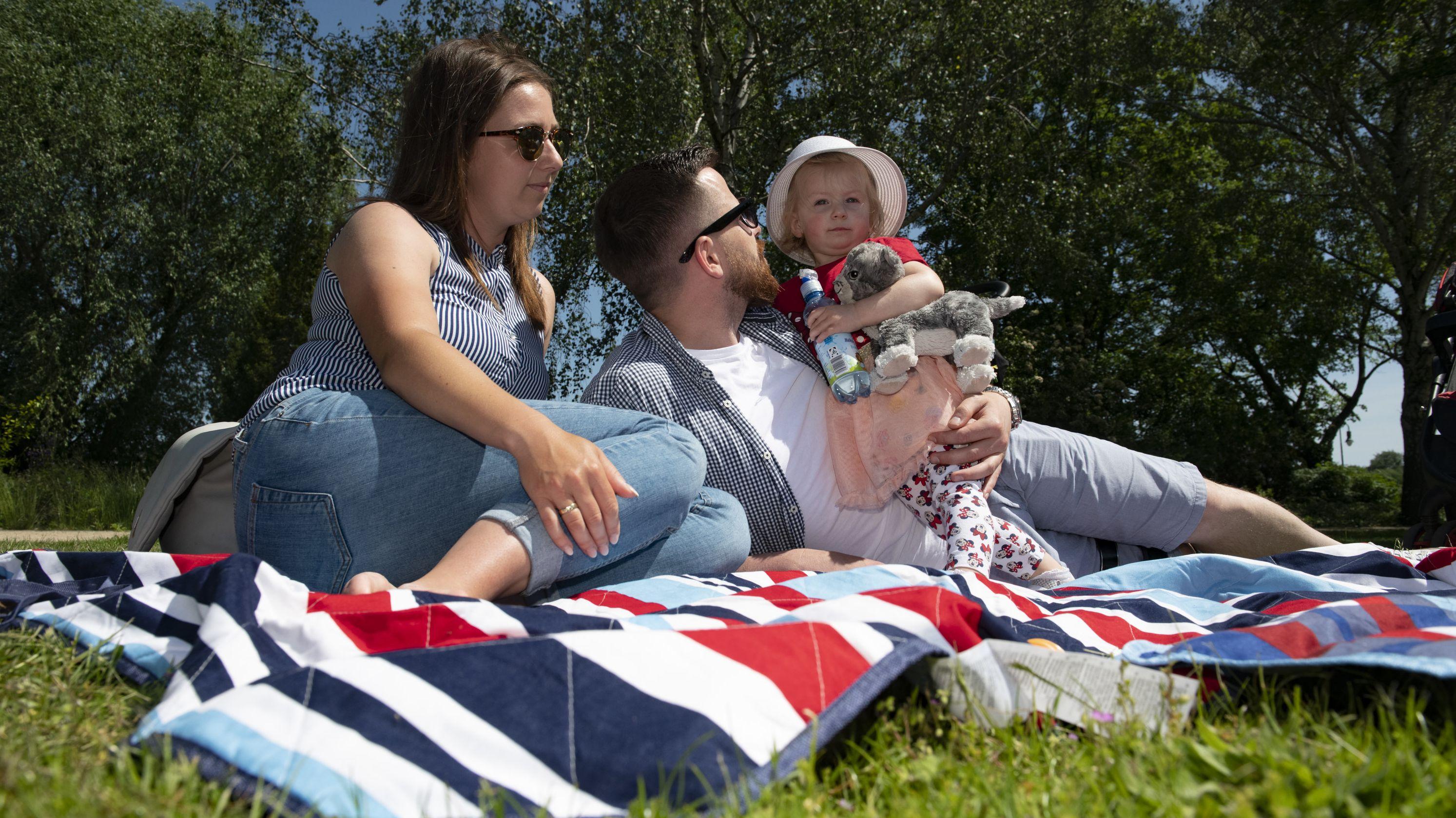 Berlin: Familie bei sonnigem Wetter auf Picknickdecke
