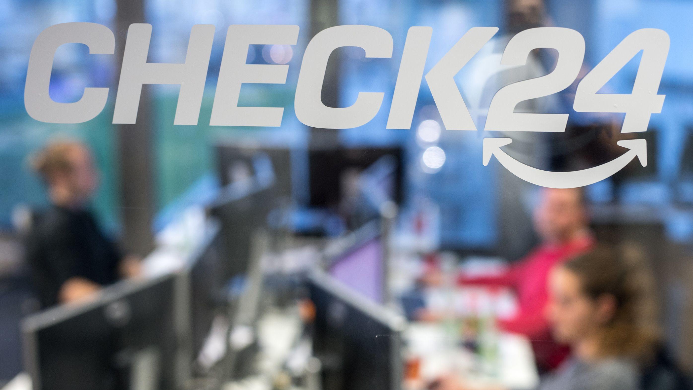 Mitarbeiter von Check24 sitzen hinter einem Logo der Firma.