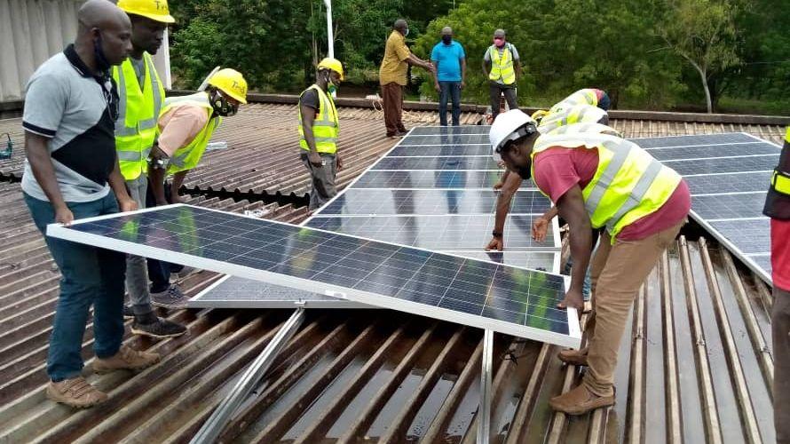 Installation einer Solaranlage auf dem Dach einer Schule.