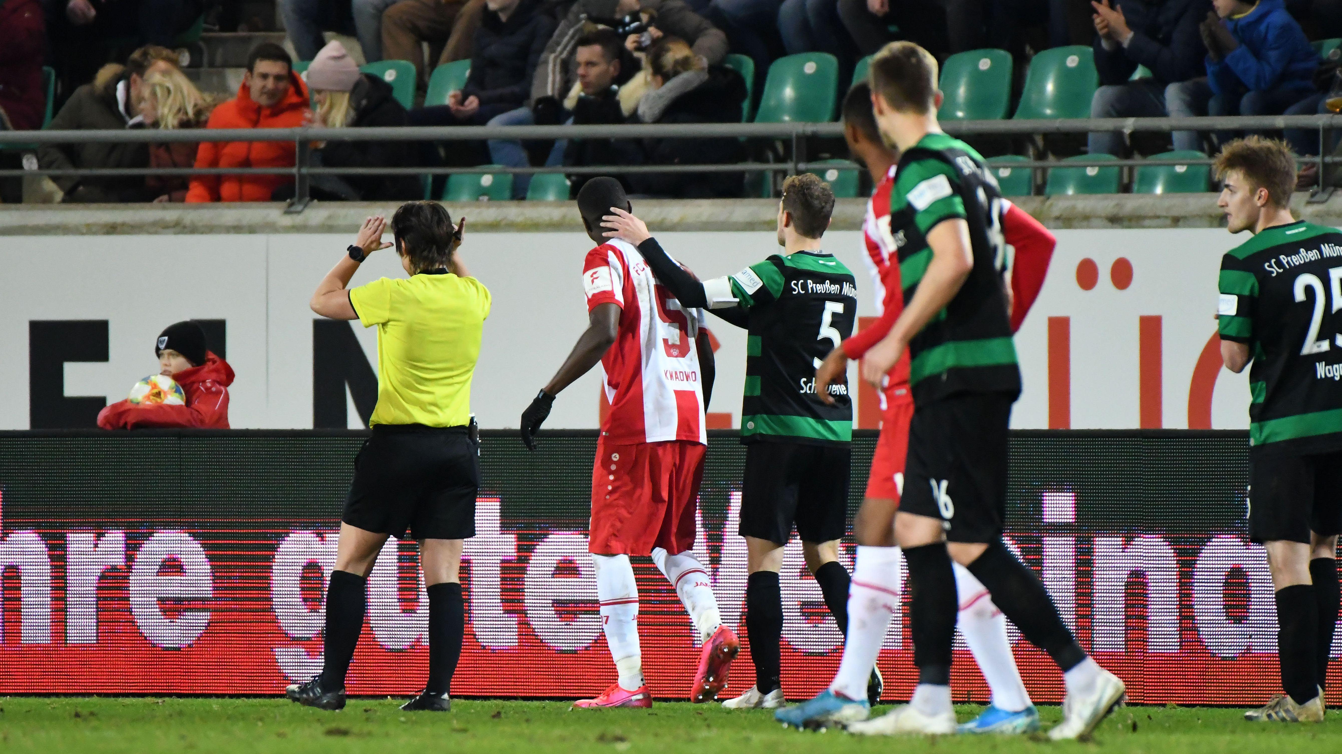 Leroy Kwadwo (FC Würzburger Kickers #5) wird rassistisch von einem Zuschauer beleidigt. Julian Schauerte (SC Preußen Münster #5) tröstet ihn.
