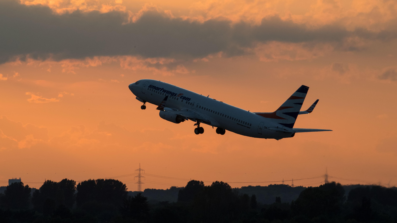 Ein Flugzeug startet in den Abendhimmel.