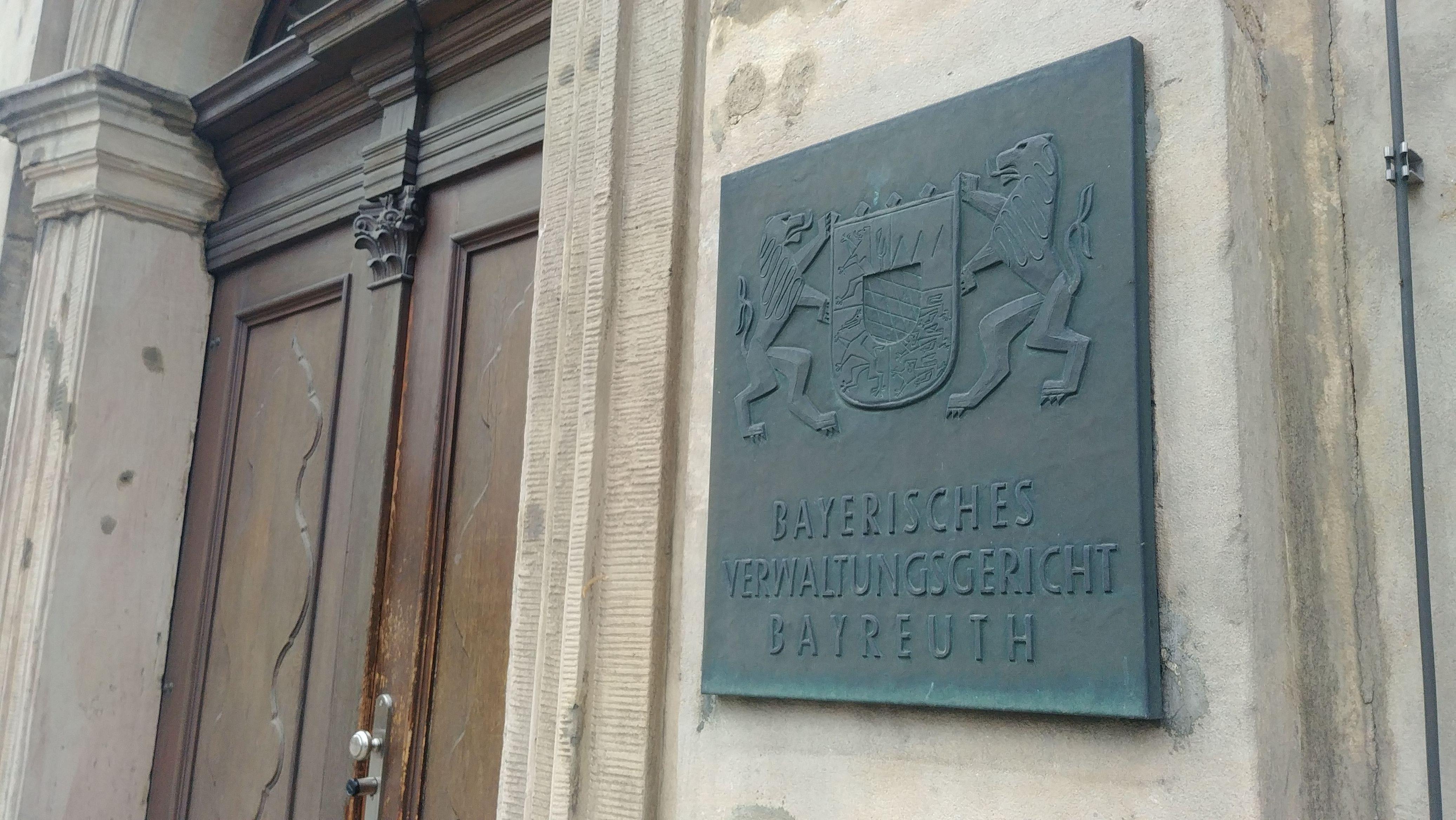 """Neben der Eingangstür befindet sich eine Tafel mit der Aufschrift """"Verwaltungsgericht Bayreuth""""."""