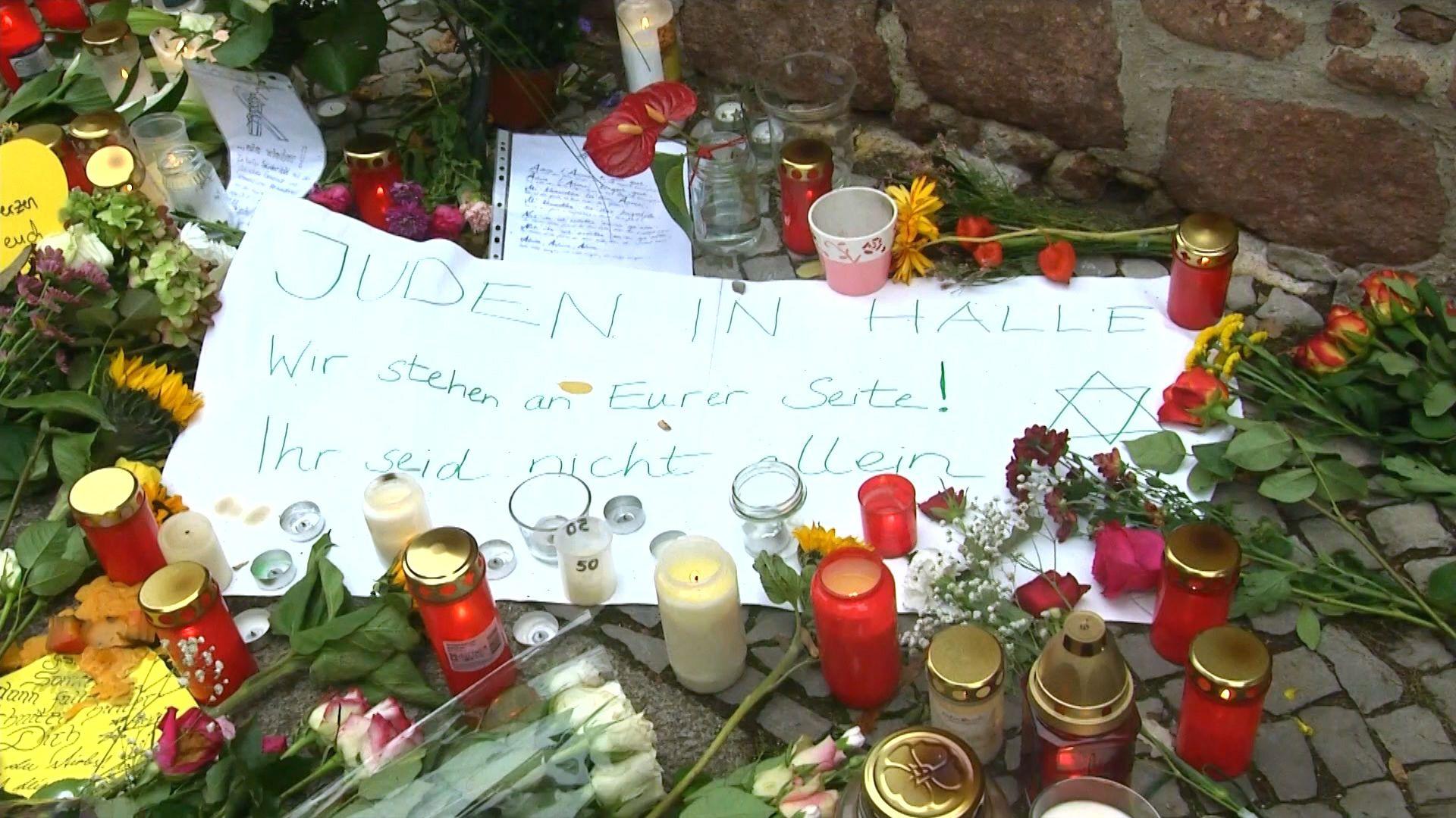 """Kerzen und Blumen vor der Synagoge in Halle. Auf einem Plakat steht: """"Juden in Halle - Wir stehen an eurer Seite! Ihr seid nicht allein."""""""