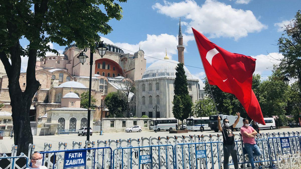 Männer mit Mundschutz und großer türkischer Flagge stehen vor einem Gitter, das die Hagia Sohpia in Istanbul absperrt