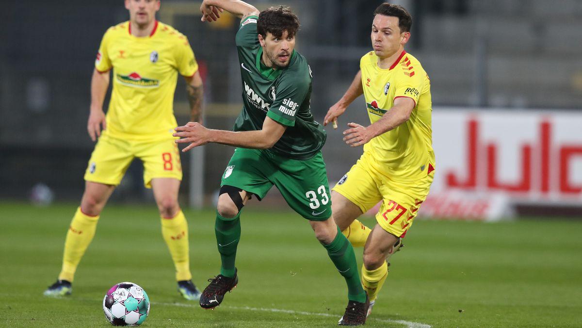 Augsburgs Tobias Strobl (M) und Freiburgs Nicolas Höfler (r) kämpfen um den Ball.