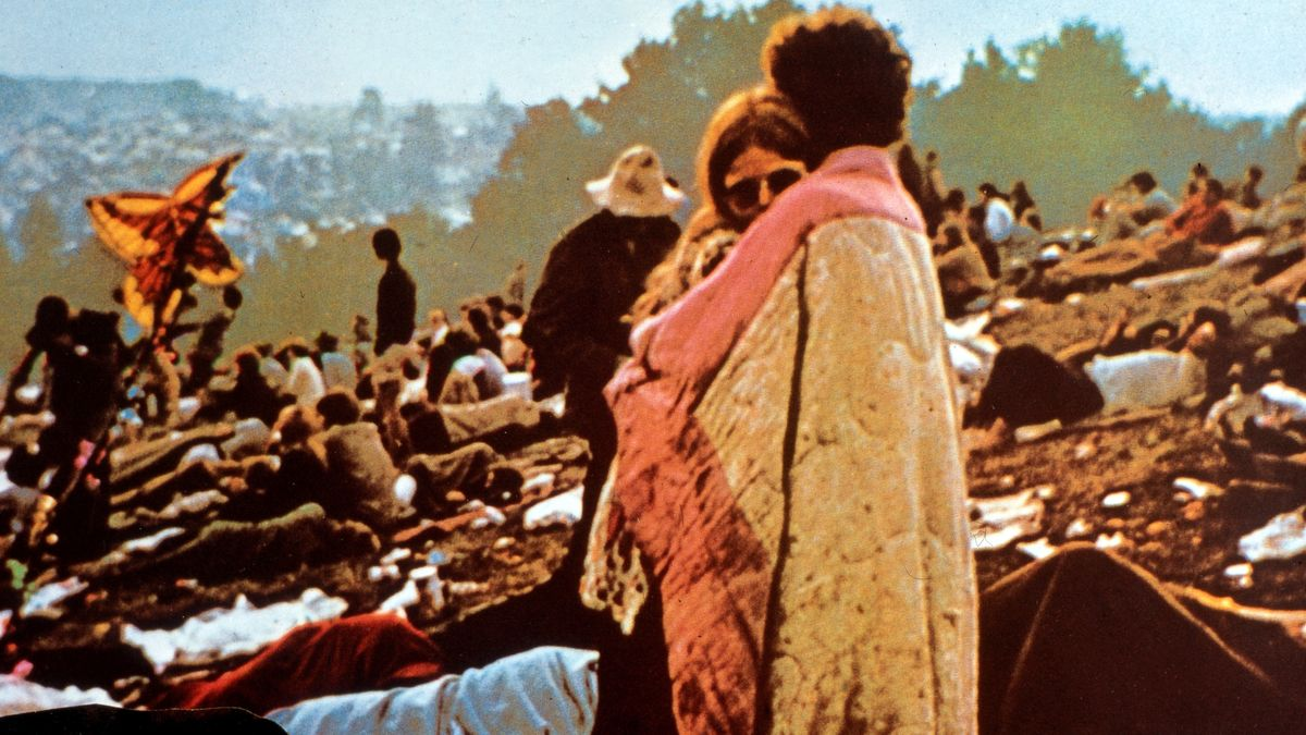 "Woodstock: Ein Paar steht, unter einer Decke aneinandergeschmiegt, auf dem Festival-Gelände von Woodstock (aus: ""Woodstock - Three Days of Love and Music"")"