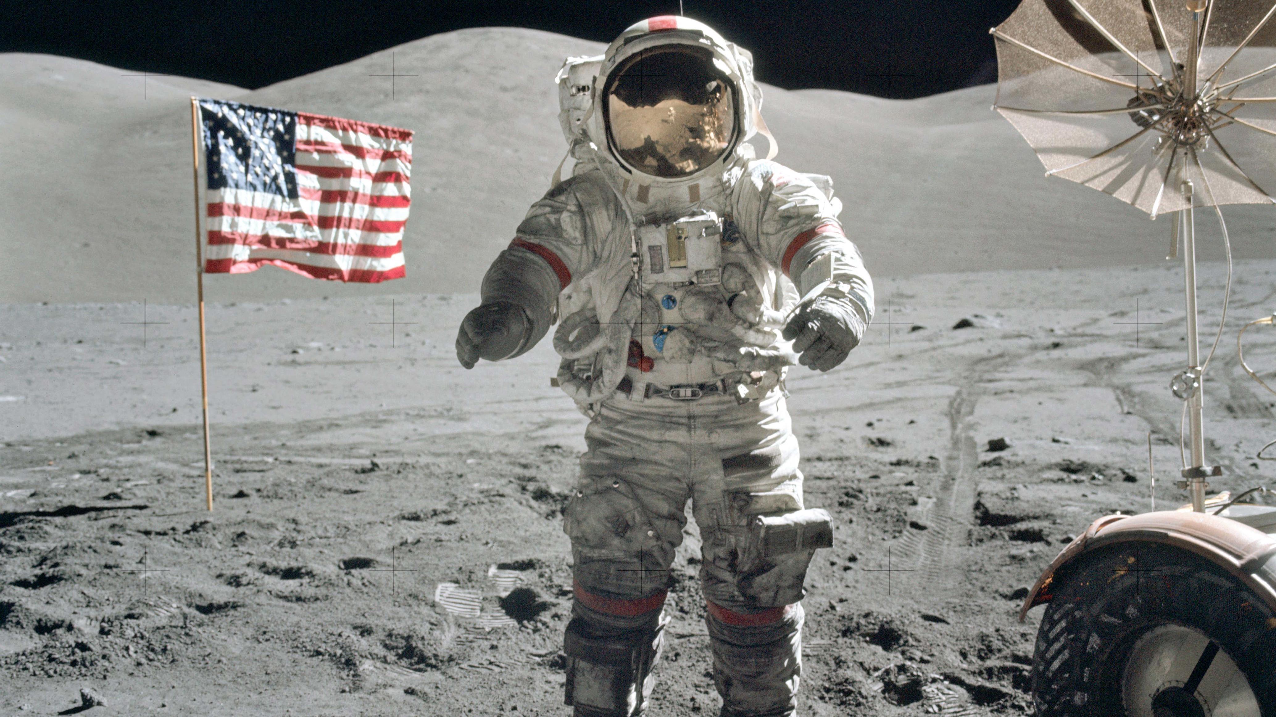 Gene Cernan, Kommandant der Apollo 17 im Dezember 1972, auf dem Mond, flankiert von amerikanischer Flagge und Mondfahrzeug.