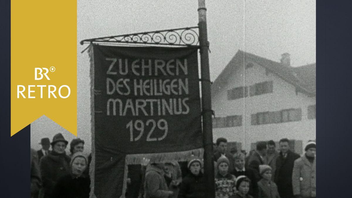 """Zuschauer beim Martiniritt in Obergünzburg. Ein Junge hält eine Fahne mit der Aufschrift """"Zu Ehren des Heiligen Martinus 1929"""