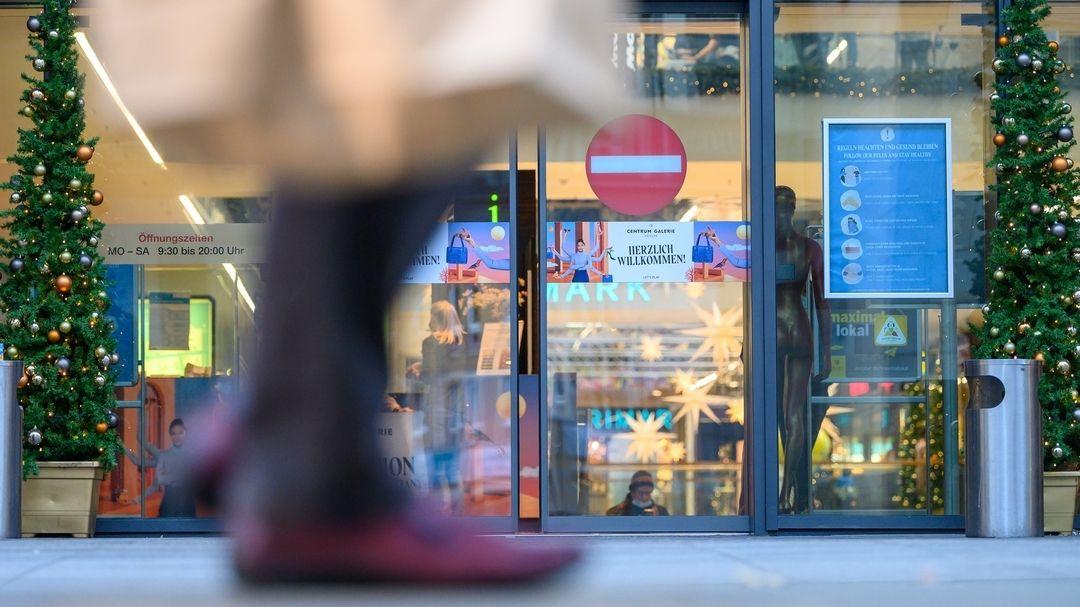 Blick auf das Schaufenster eines Kaufhauses mit Weihnachtsdekoration. Auf dem Eingang ein Hinweis auf Eintrittsverbot. Im Vordergrund geht eine Passantin vorbei.