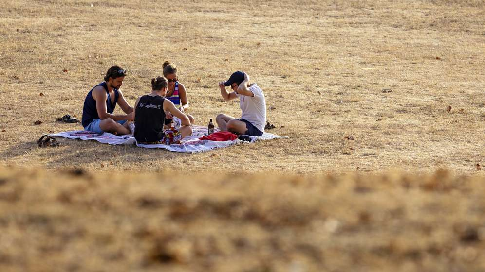 junge Erwachsene auf einer verdorrten Wiese im Hitzesommer 2018: hohe Temperaturen und geringe Niederschläge führten zu extremer Dürre. | Bild:picture alliance/Geisler-Fotopress