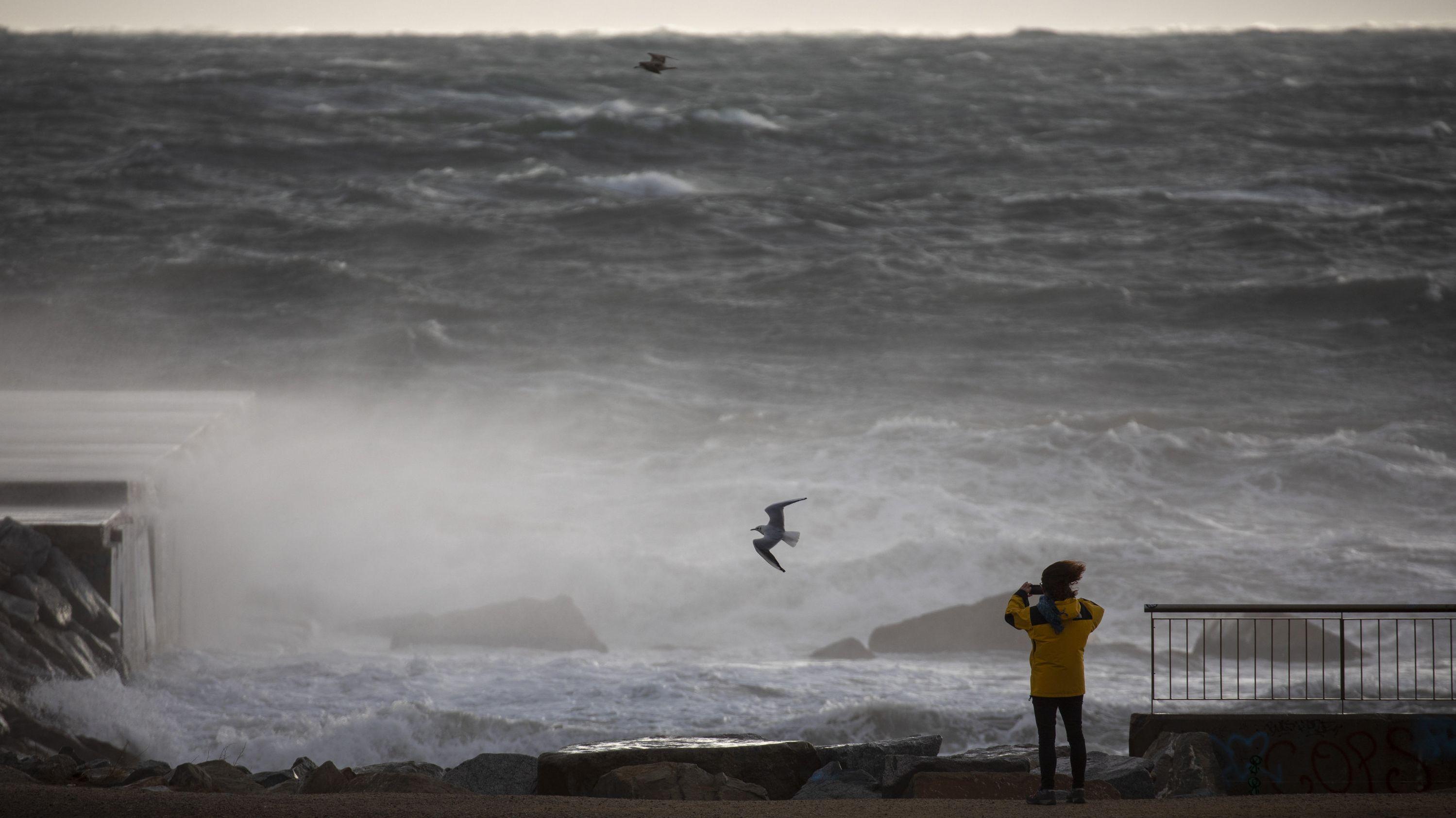 Eine Frau fotografiert das Mittelmeer bei starkem Wind in Barcelona. Schnee und Unwetter haben im Osten Spaniens Stromausfälle, Zugverspätungen und Rekordwellen ausgelöst.