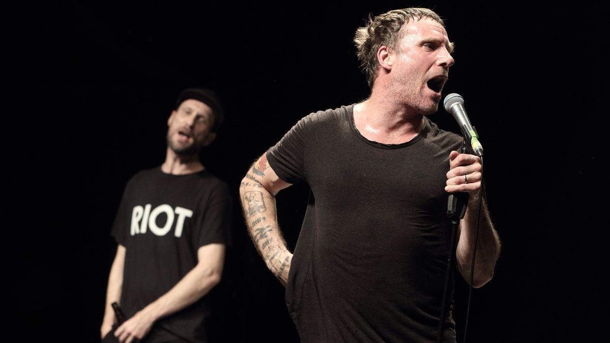 Sleaford Mods, ein Duo aus der Nähe von Nottingham, steht in schwarzen Shirts auf der Bühne und singen.