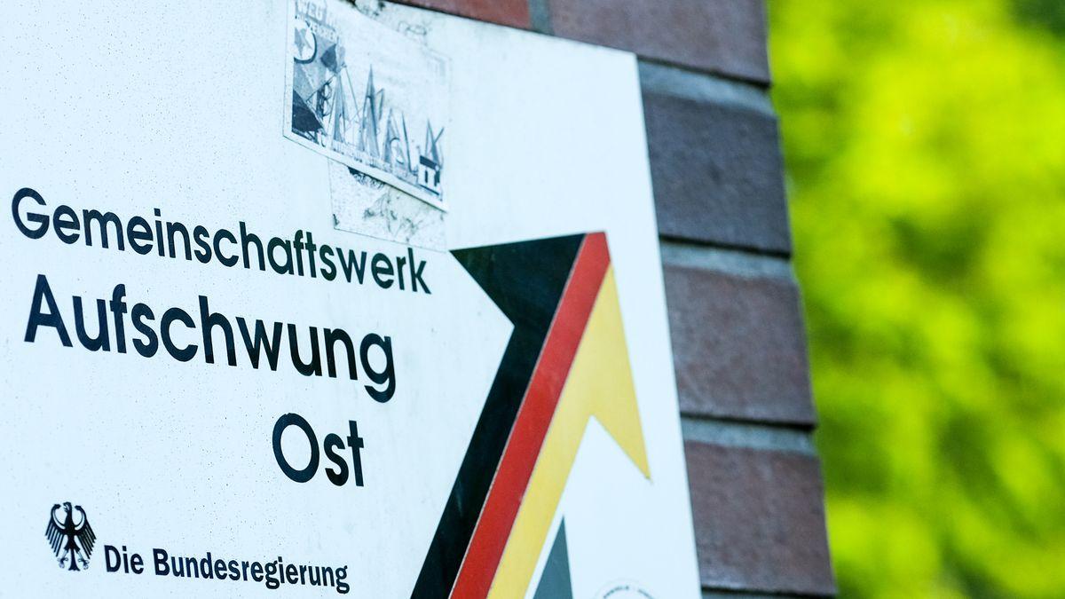 """Ein Schild mit der Aufschrift """"Gemeinschaftswerk Aufschwung Ost"""" ist an einer Häuserwand angebracht. Am 8. März 1991 wurde das Programm von der Bundesregierung beschlossen. Damit sollte die ostdeutsche Wirtschaft gefördert werden."""